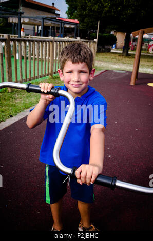 child climbs on games at the playground - Stock Photo