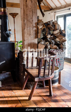 Welsh chair and firewood in Sussex barn conversion - Stock Photo