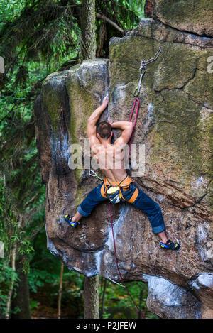 Karpniki, Poland, 12 june 2018. A man climbing a rock in Sokoliki in Poland. - Stock Photo