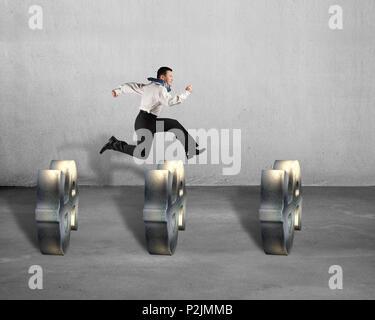 Businessman jumping over USD symbols concrete background - Stock Photo