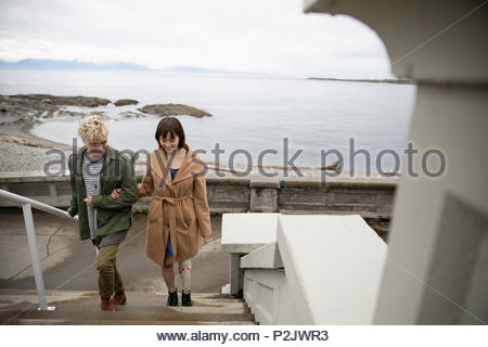 Young woman amputee walking with boyfriend up stairs overlooking beach - Stock Photo