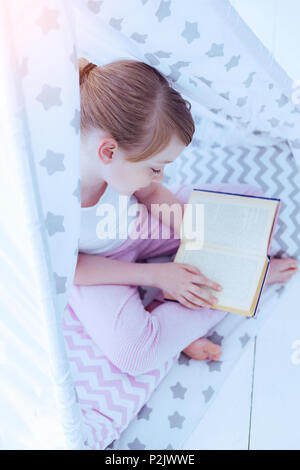 Adorable preteen girl reading fairytale in teepee - Stock Photo