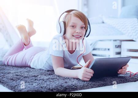 Joyful girl with headphones smiling into camera - Stock Photo