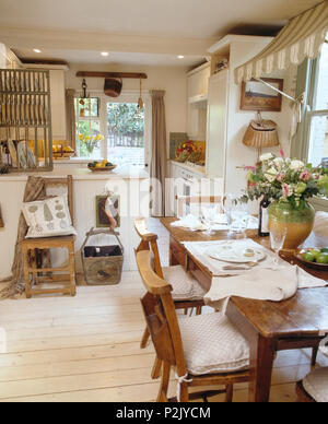 Old chapel chairs at simple wood table in country kitchen dining room with white painted floorboards - Stock Photo