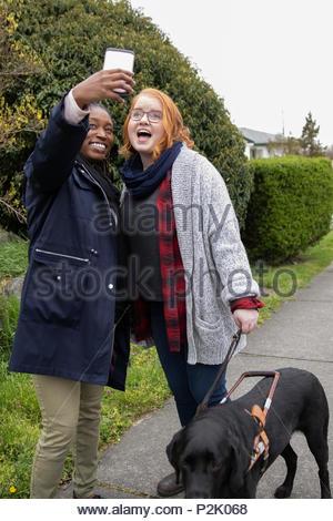 Women friends with seeing eye dog taking selfie on sidewalk - Stock Photo