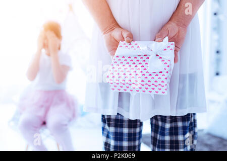 Loving daddy hiding gift prepared for his daughter - Stock Photo