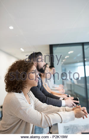 Forward looking, ambitious business people at office railing - Stock Photo