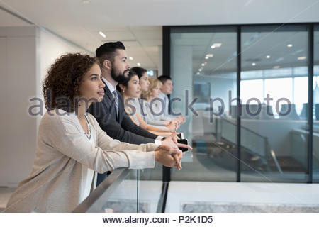 Forward looking business people standing at office railing - Stock Photo