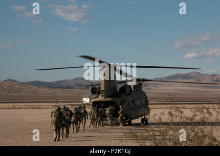 British soldiers from 1st the Queen's Dragoon Guard board a U.S. Army 1st Air Cavalry Brigade CH-47 Chinook aircraft to embark on an air assault mission Sep. 30, 2016 to provide reconnaissane support in preparation for the 3rd Armored Brigade Combat Team, 1st Cavalry Division's push into the 'box' to kick off the force-on-force fight during National Training Center (NTC) 17-01 at Fort Irwin, Calif. The 155th Armored Brigade Combat Team from the Mississippi National Guard, partnership played a major role in the execution of the brigade's training rotation. NTC 17-01 provides U.S. military units - Stock Photo