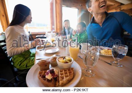 Family enjoying waffle breakfast at cabin table - Stock Photo