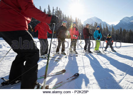 Family receiving group ski lesson from ski resort instructor - Stock Photo