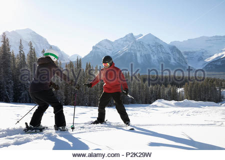 Woman receiving ski lesson from ski resort instructor - Stock Photo