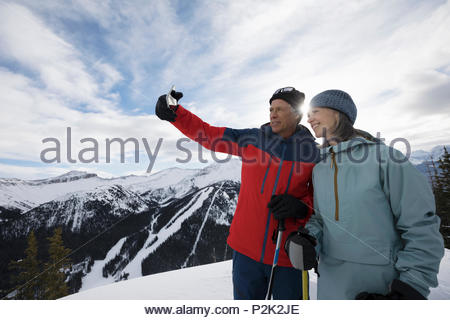 Senior couple skiers taking selfie on sunny mountain - Stock Photo