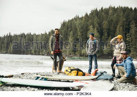 Friends with dog enjoying weekend surfing getaway next to surfboards on rugged beach - Stock Photo