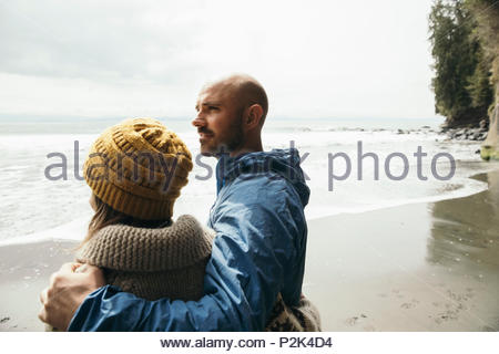 Couple standing on rugged beach - Stock Photo