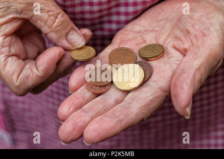 An elderly lady holds a few cents of euro in her hands. - Stock Photo