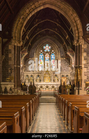 Fort William, Scotland - June 11, 2012: Inside Saint Andrews Church shows part of nave, the chancel, the altar and the monumental stone backdrop. Stai - Stock Photo