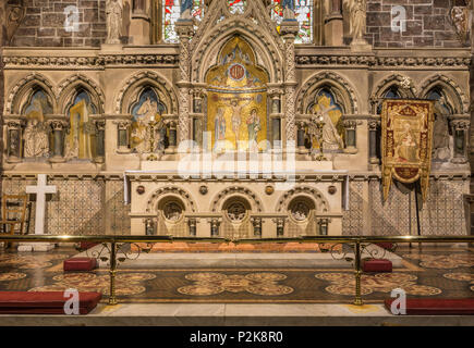 Fort William, Scotland - June 11, 2012: Inside Saint Andrews Church shows the modern altar in front of stone artwork backdrop. - Stock Photo