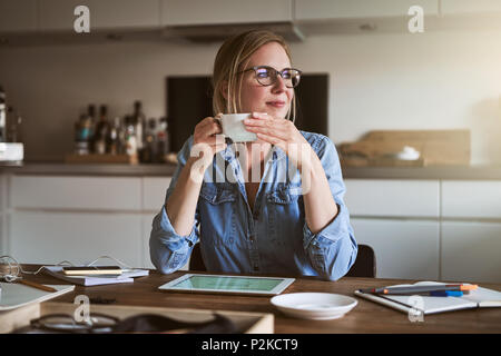 Smiling female entrepreneur looking through a window while drinking coffee and working at a table in her kitchen - Stock Photo