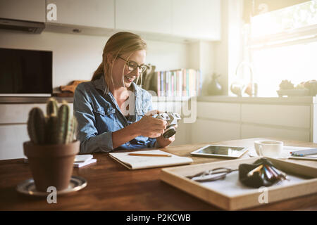 Smiling young female photographer looking at images on her camera while sitting at her kitchen table at home - Stock Photo
