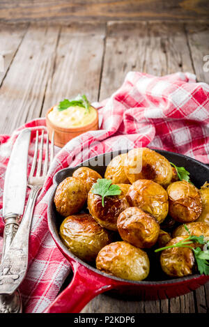 Baked in frying pan whole young potatoes, homemade vegetarian food, wooden old rustic table, with sauce, copy space - Stock Photo