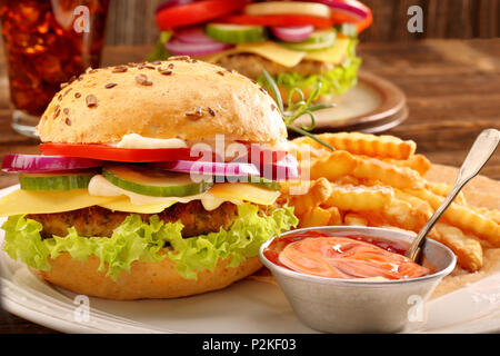 Fresh tasty burger with fries and beer on wooden table - Stock Photo