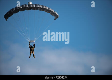 A pararescueman (PJ) glides through the air during a high-altitude, low opening (HALO) team competition in Sebastian,  Florida, Sept. 19, 2016.  The HALO jump is a method of delivering personnel, equipment, and supplies from a transport aircraft at a high altitude via free-fall parachute insertion. The event was part of the 2016 PJ Rodeo, which brought together past and present PJs from around the world, to showcase their unique mission and build camaraderie. (U.S. Air Force photo/Tech. Sgt. Brandon Shapiro) - Stock Photo