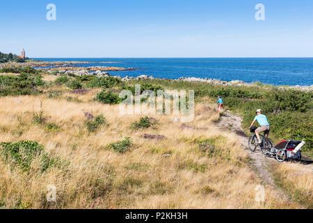 Svaneke lighthouse, rocky coast, summer, family on a cycle tour, Baltic sea, Bornholm, Svaneke, Denmark, Europe - Stock Photo