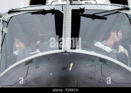 Festivalgoers sit the cockpit of a U.S. Air Force UH-1N Iroquois helicopter during the 43rd Anniversary Event of Japan Ground Self-Defense Force Camp Tachikawa at JGSDF Camp Tachikawa, Japan, Oct. 1, 2016. Service members with the 459th Airlift Squadron from Yokota Air Base and Army Aviation Battalion from Camp Zama participated in the festival. (U.S. Air Force photo by Yasuo Osakabe/Released) - Stock Photo