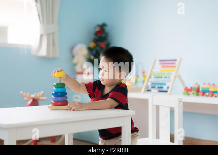 Adorable Asian Toddler baby boy sitting on chair and playing with color developmental toys at home. - Stock Photo
