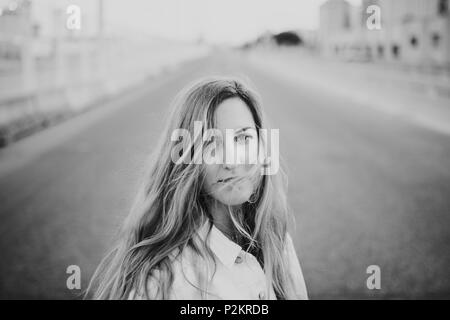 Black and white close up portrait of blonde woman posing in the middle of the road.