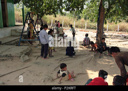 Cambodian children playing on the bare earth of the playground at Ream Village School, Sihanouk province. - Stock Photo