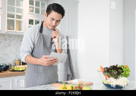 Asian confused man reading his tablet with a pensive thoughtful look while standing in his kitchen while cooking and preparing a meal from a variety o - Stock Photo