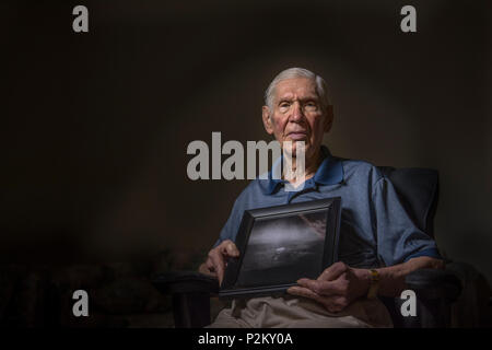 Russell Gackenbach, the navigator aboard the B-29 Superfortress, Necessary Evil, holds a photo he took during the atomic bombing mission over Hiroshima, Japan on Aug. 6, 1945. Gackenbach is the last surviving crew member from the three B-29s that flew the mission. (U.S. Air Force photo/Master Sgt. Brian Ferguson) - Stock Photo