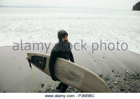 Male surfer in wet suit carrying surfboard on rugged beach - Stock Photo