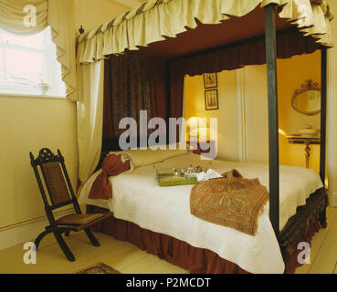 Cream and brown drapes on four-poster bed in cream bedroom with Victorian chair beside bed - Stock Photo