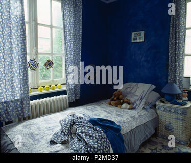Blue+white curtains on window above single bed with blue+white quilt in child's blue bedroom - Stock Photo
