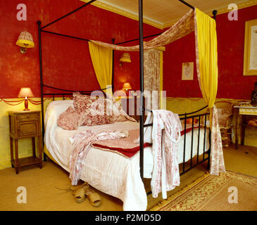 Toile-de-Jouy and yellow drapes on metal four-poster bed with white quilt and Toile-de-Jouy cushions in red French bedroom - Stock Photo