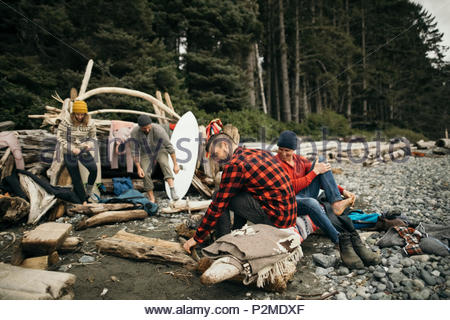 Friends enjoying weekend surfing getaway, relaxing at campsite on rugged beach - Stock Photo