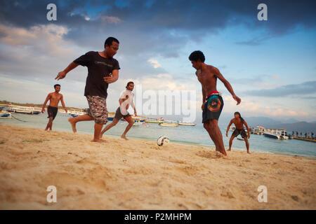Young locals playing football on Trawangan beach, Gili Trawangan, Lombok, Indonesia - Stock Photo