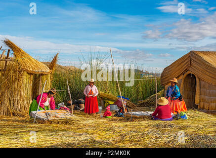 A group of Uros indigenous on the floating islands made of Totora reed in the Titicaca Lake near Puno, Peru. - Stock Photo