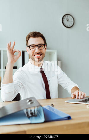 stylish smiling businessman with laptop and documents showing ok sign at workspace - Stock Photo