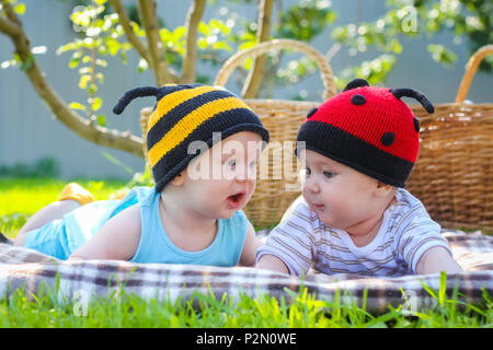 Picture of brother and sister having fun in the park, two cheerful children laying down on green grass, little girl and boy playing outdoors, best fri - Stock Photo