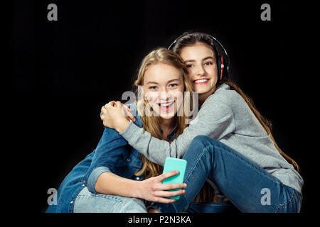 teen girls using smartphone and embracing isolated on black - Stock Photo