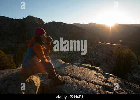 Woman drinking coffee at sunrise deep in the Ansel Adams Wilderness. High Sierra backpacking trip to Garnet Lake and Nydiver Lake. - Stock Photo