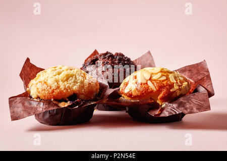 Almond, blueberry and chocolate muffins in brown paper on pink background - Stock Photo