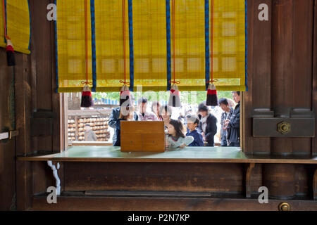 Japanese family drawing fortune telling paper at Meiji Shrine, Shibuya, Tokyo, Japan - Stock Photo