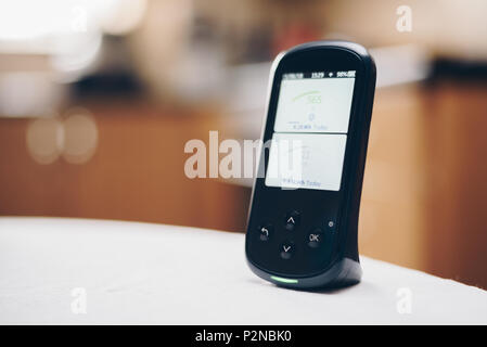Domestic Energy Smart Meter on a Kitchen Worktop Displaying Energy Usage in Real Time - Stock Photo