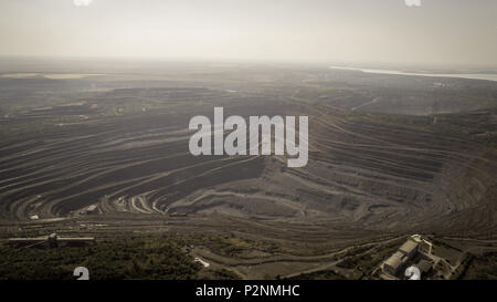 Aerial view of opencast mining quarry with lots of machinery at work. Retro - Stock Photo