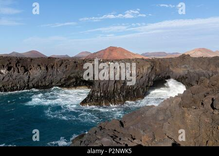 Spain, Canary Islands, Lanzarote Island, The ocean rages on the rock formation of Los Hervideros with the volcanoes of Timanfaya in the background - Stock Photo